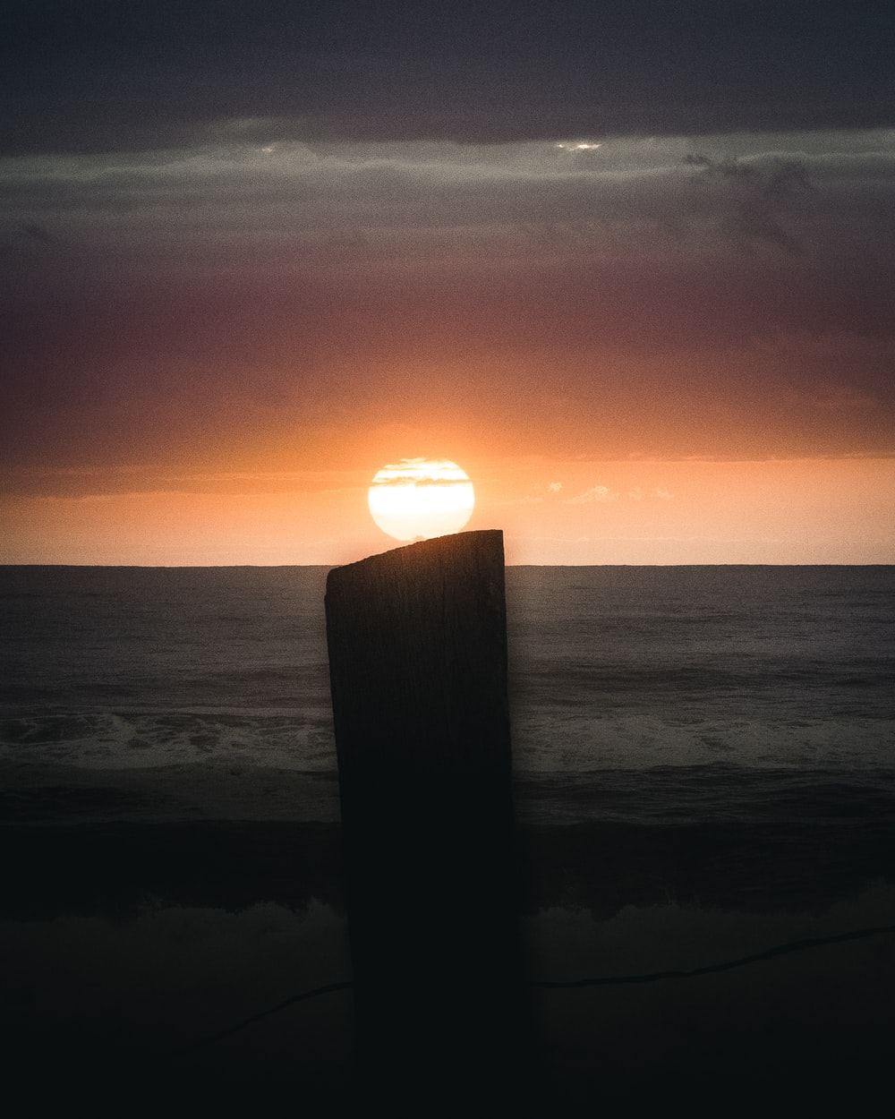 brown wooden post on sea shore during sunset