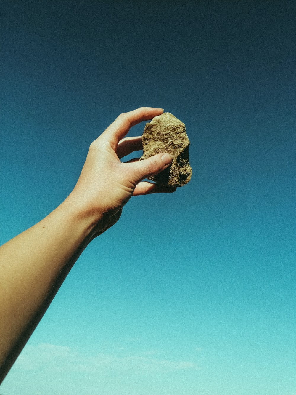 person holding brown rock under blue sky during daytime