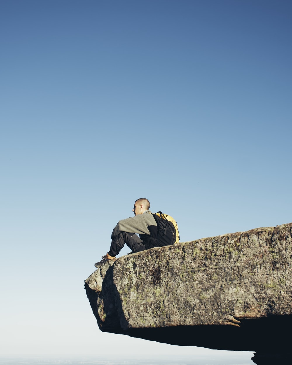man in black jacket sitting on gray rock during daytime