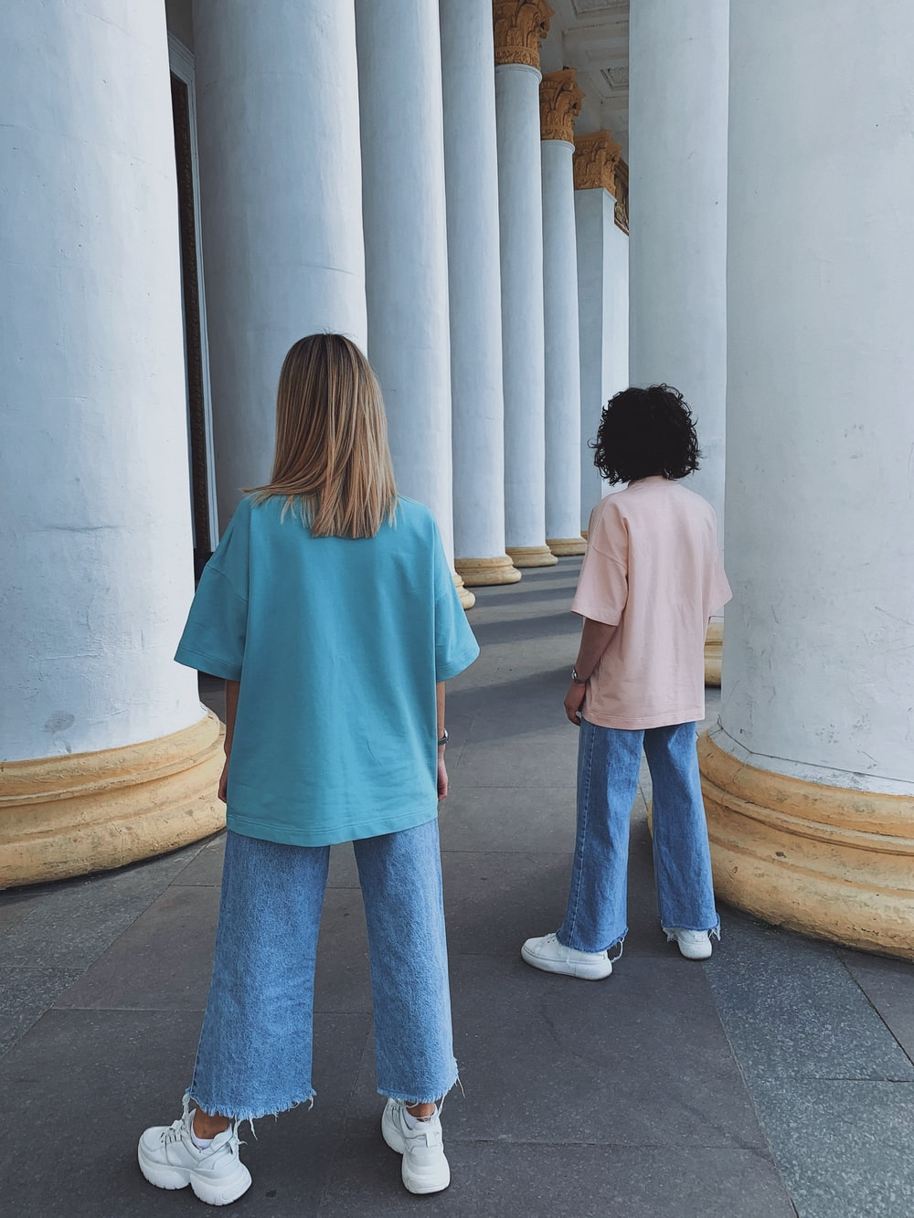 2 women standing in front of white wall