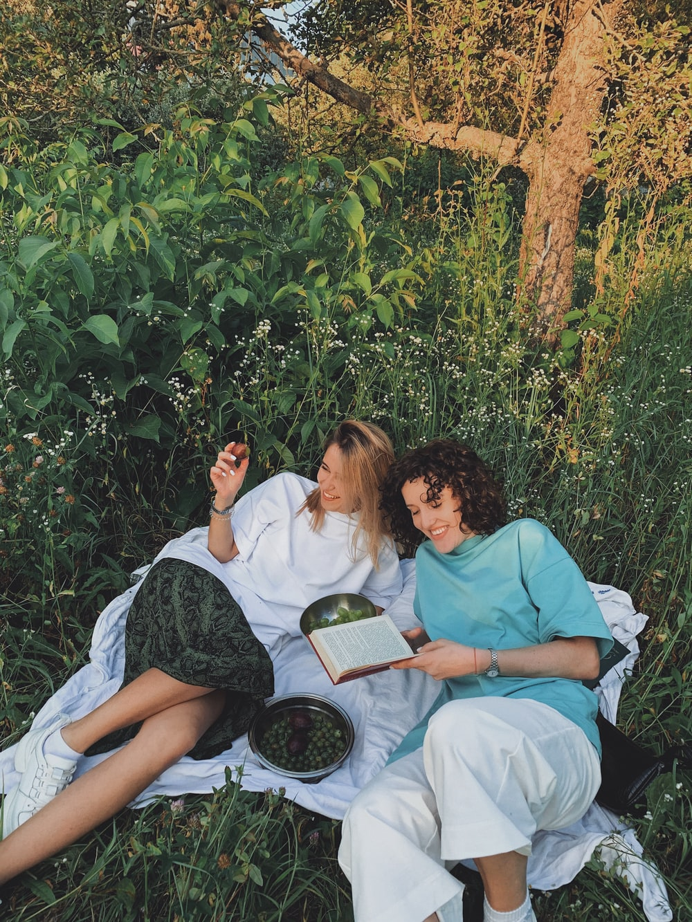 man and woman sitting on white bed reading book