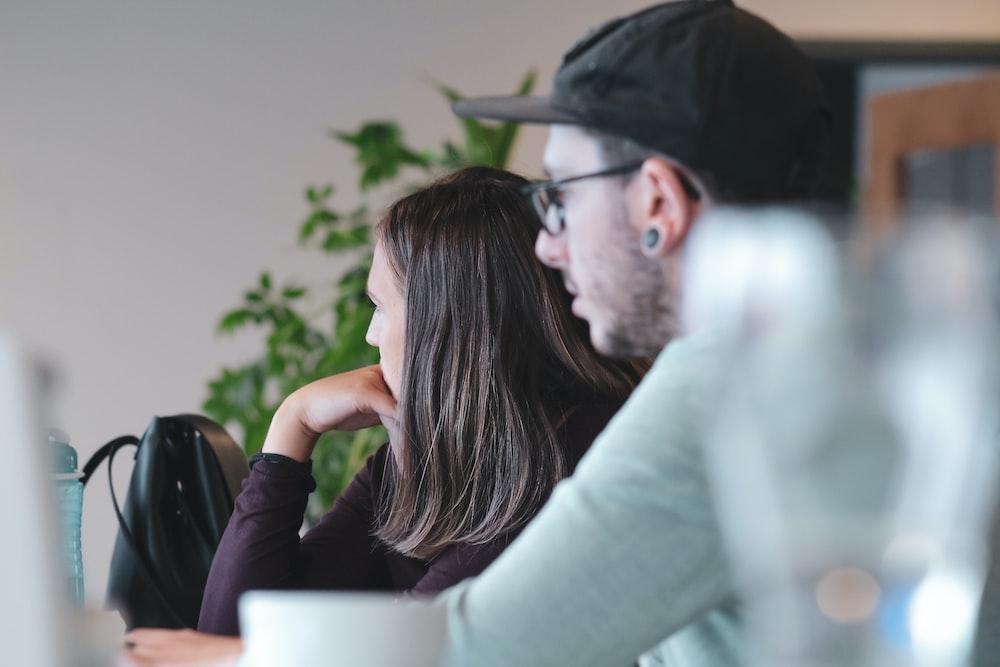 man in white long sleeve shirt sitting beside woman in black shirt