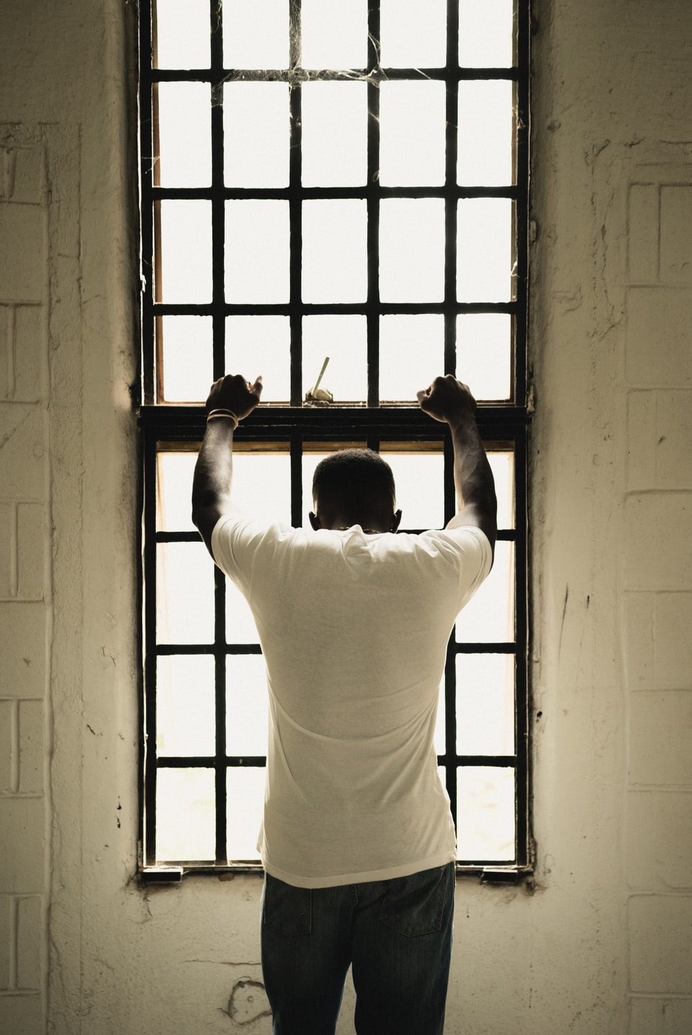 man in white t-shirt standing in front of window