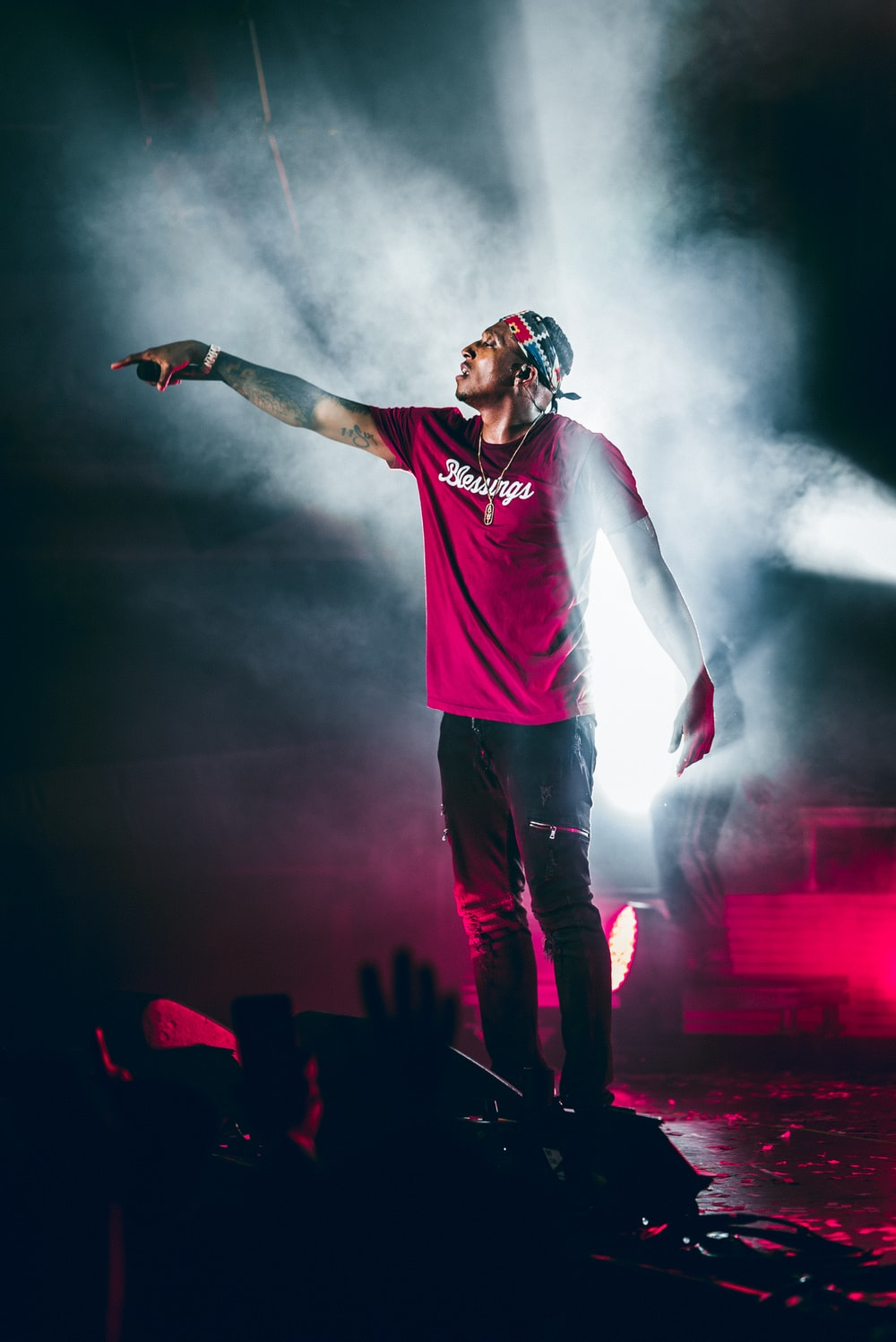 man in red crew neck t-shirt and blue denim jeans standing on stage