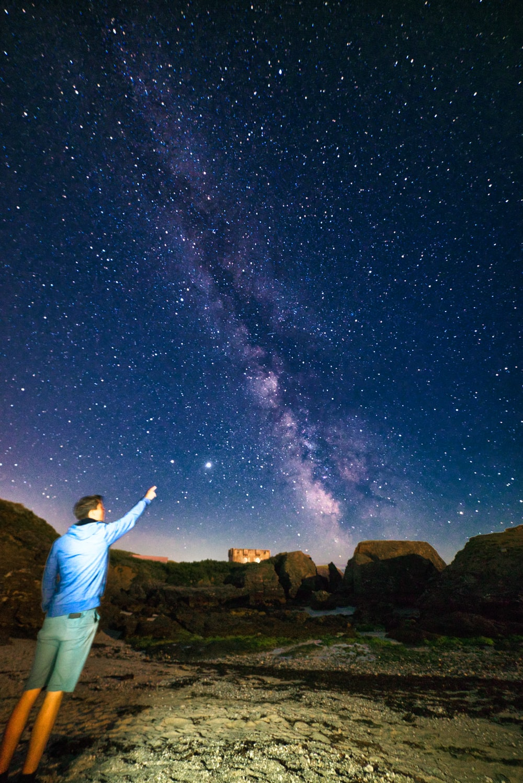 man in white dress shirt standing on brown rock under starry night