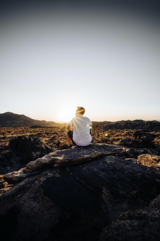 man in white shirt sitting on brown rock during daytime