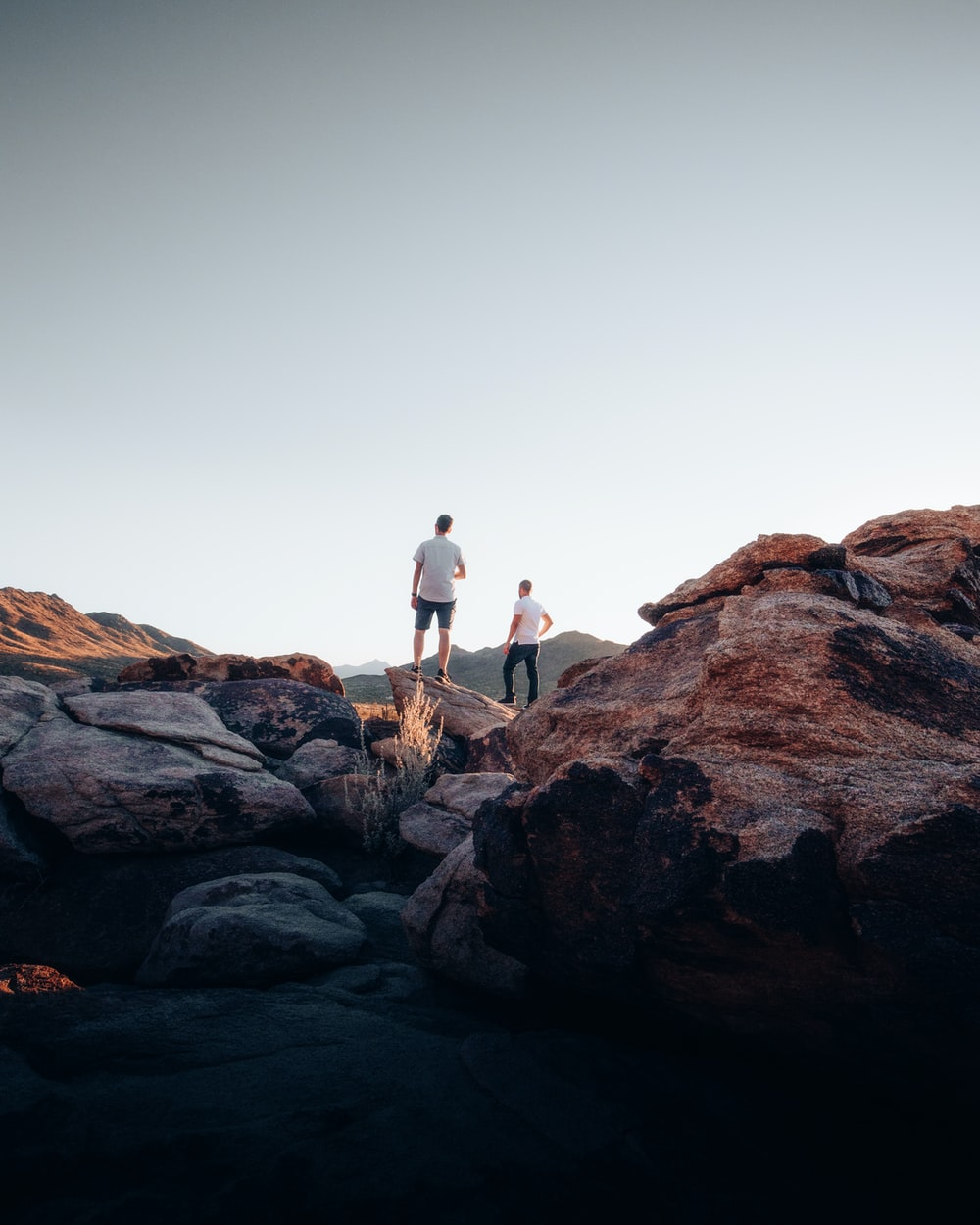 man and woman standing on brown rock formation during daytime