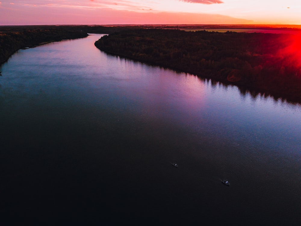 body of water near brown field during sunset