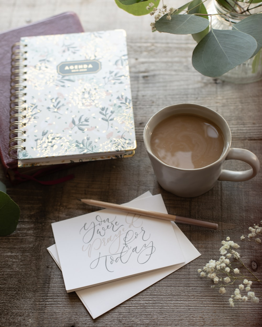 white and purple floral notebook beside white ceramic mug