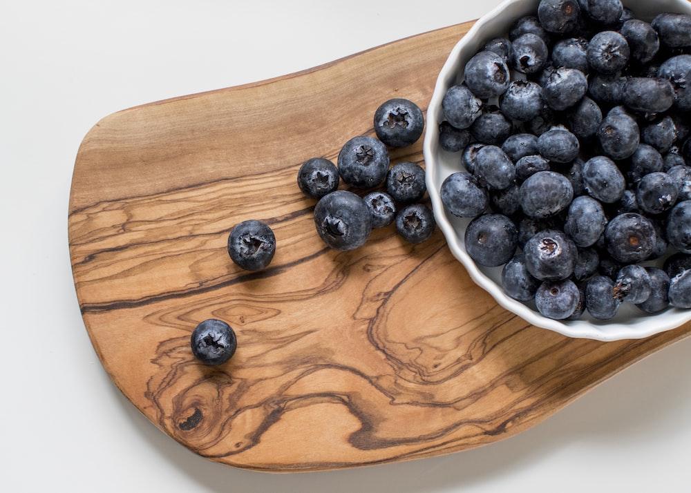 black berries on brown wooden chopping board