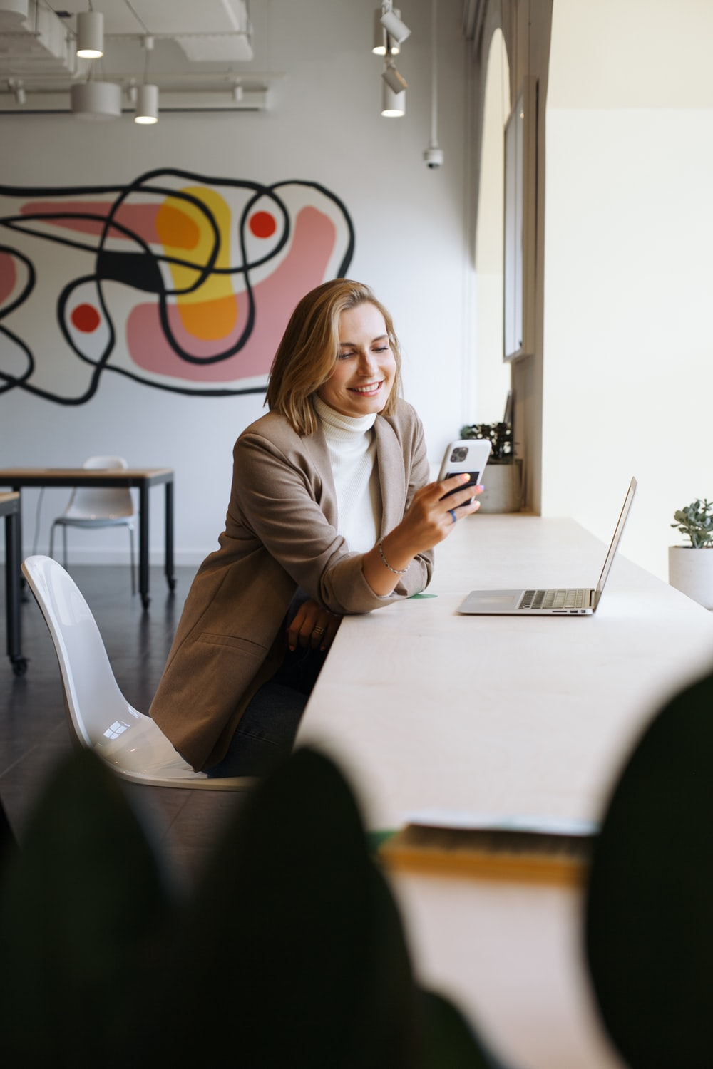 woman in brown blazer sitting on chair holding smartphone