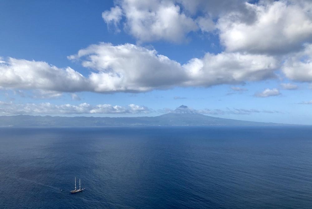 white and blue sky over blue sea