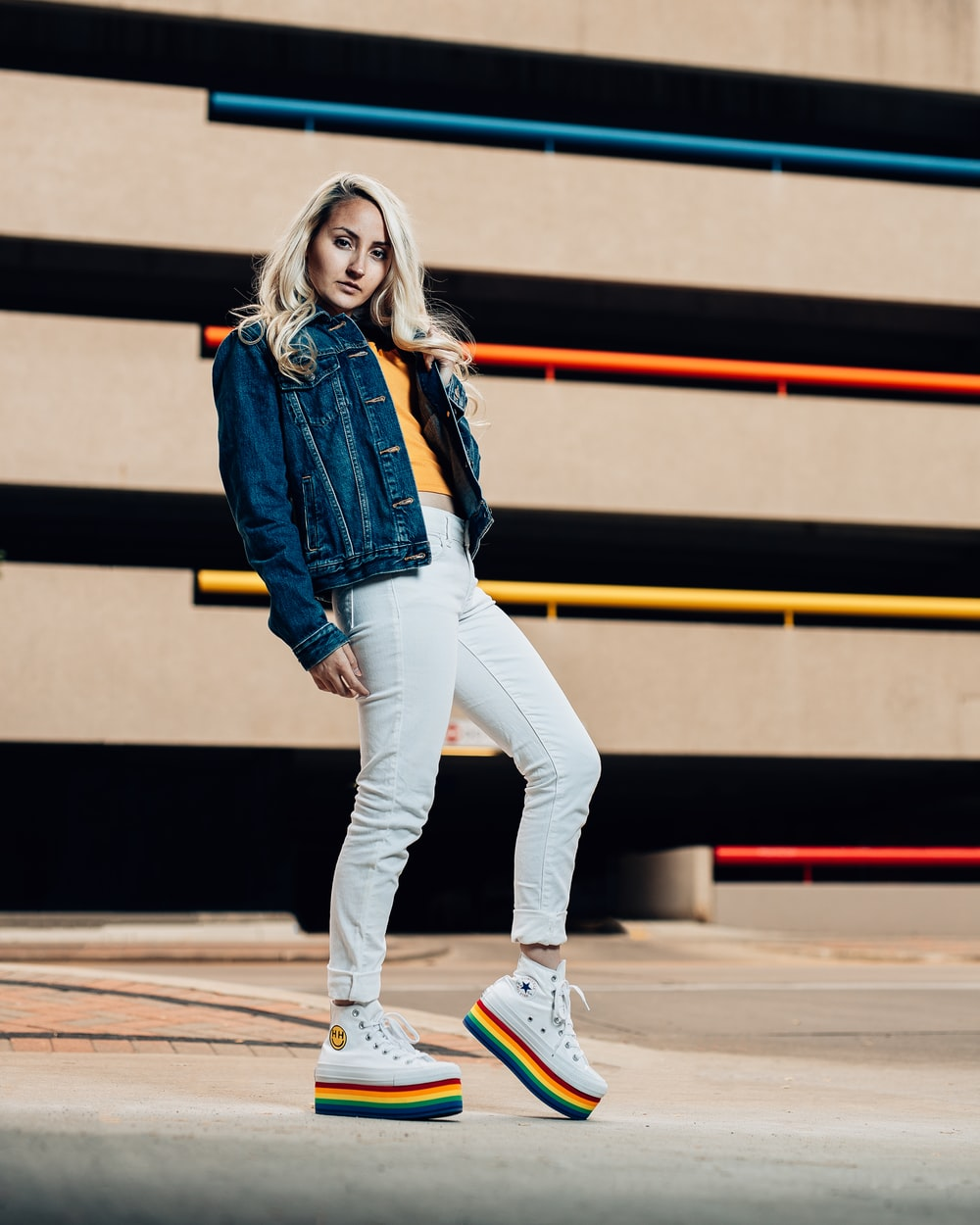 woman in blue denim jacket and white pants wearing white sneakers