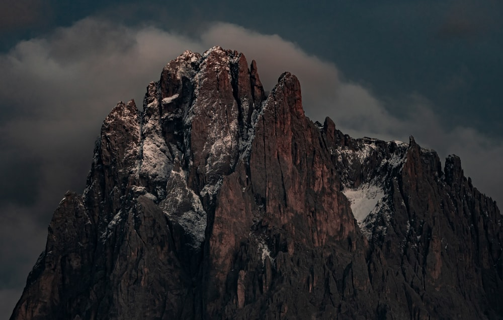 brown rocky mountain under gray sky