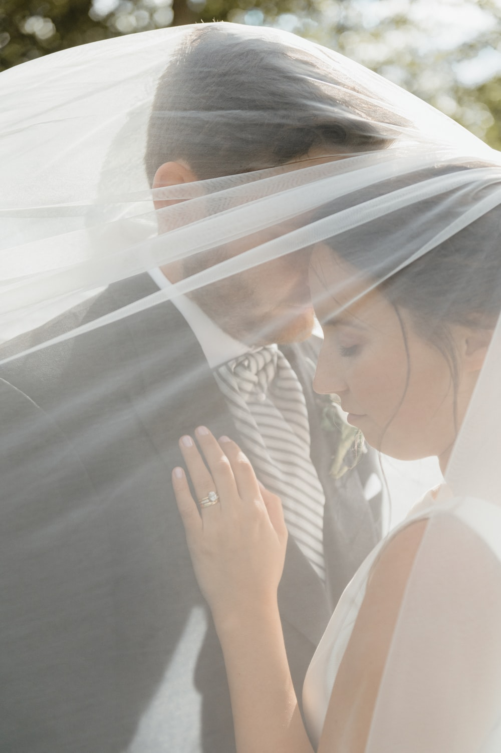 woman in white dress shirt covering her face with white veil