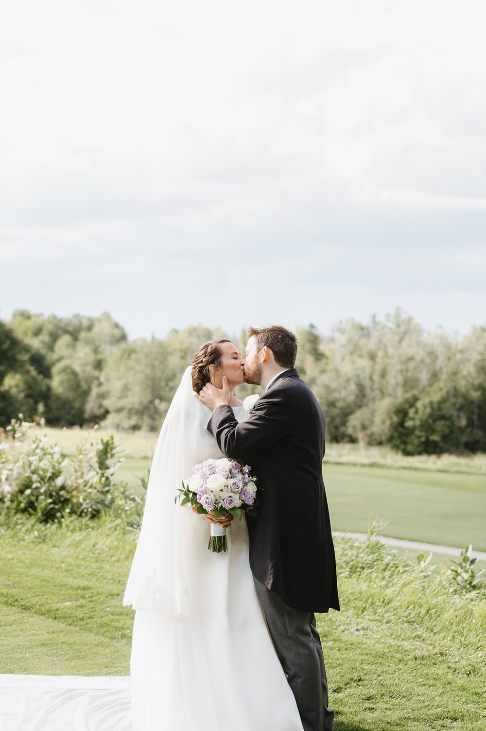 man and woman kissing on green grass field during daytime