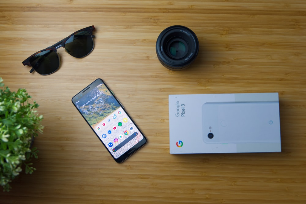 white iphone 5 c beside black sunglasses