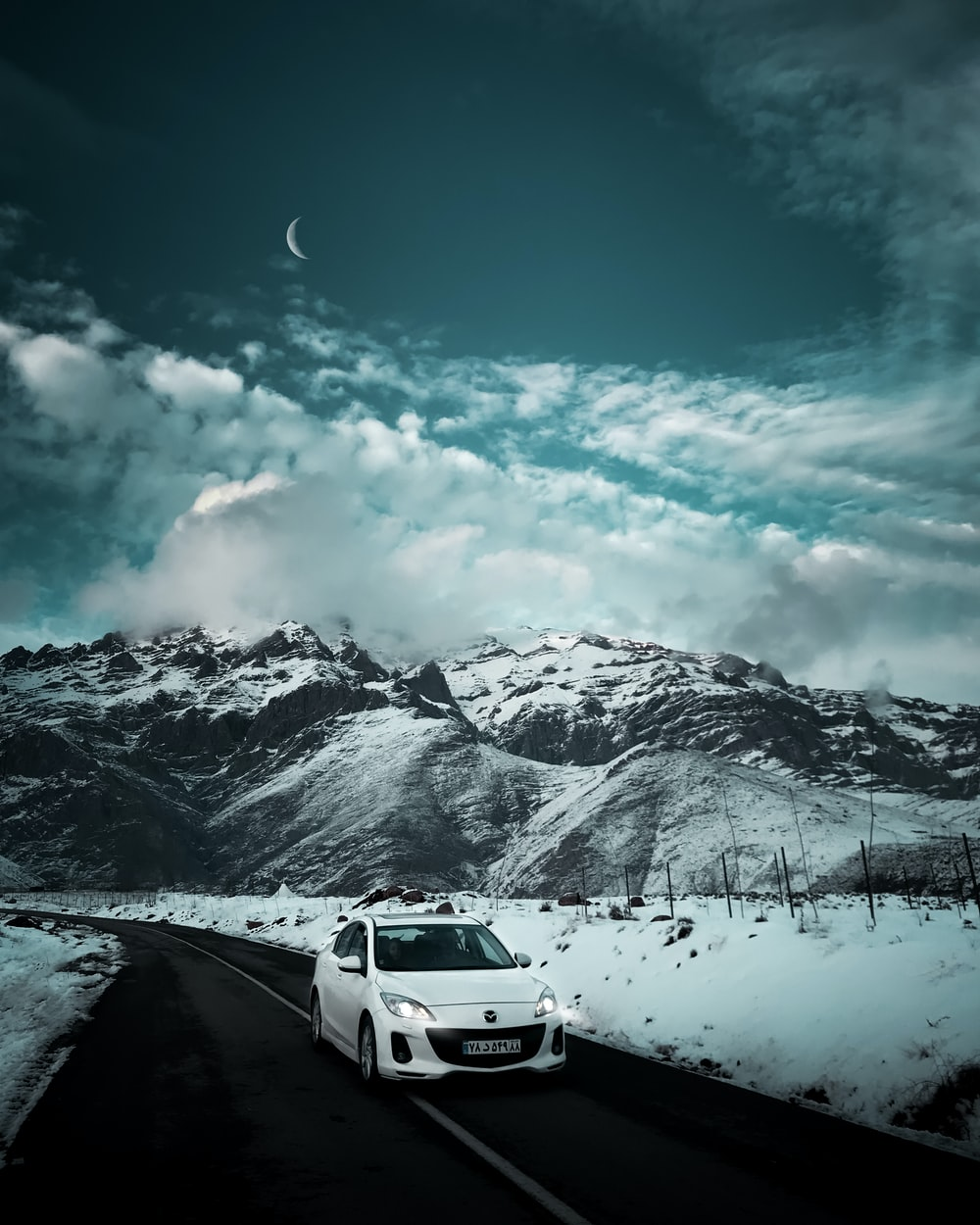 white car on snow covered ground under blue sky and white clouds during daytime
