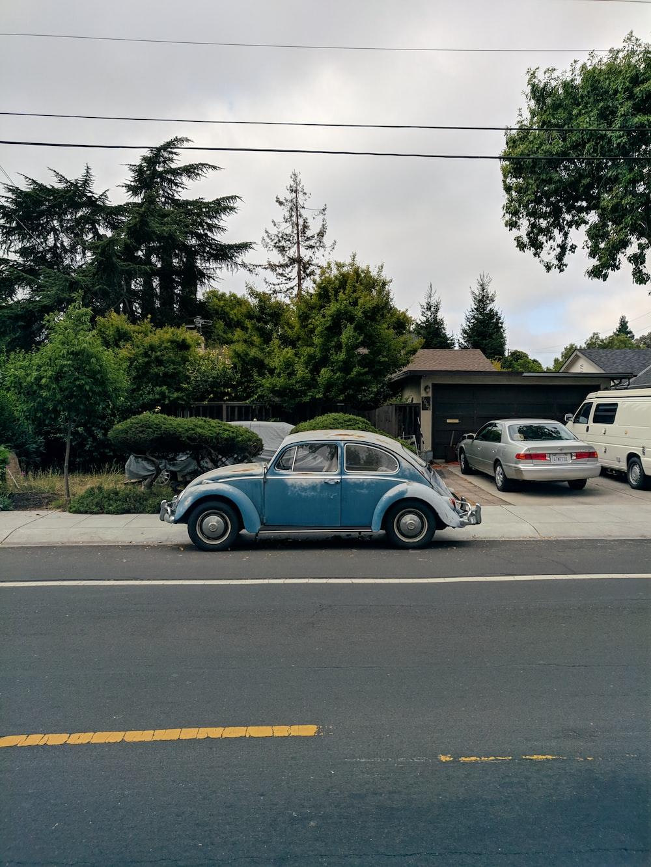 blue volkswagen beetle parked on parking lot during daytime