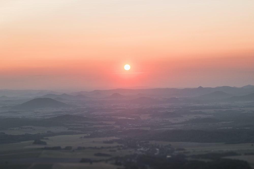 mountains under orange sky during sunset