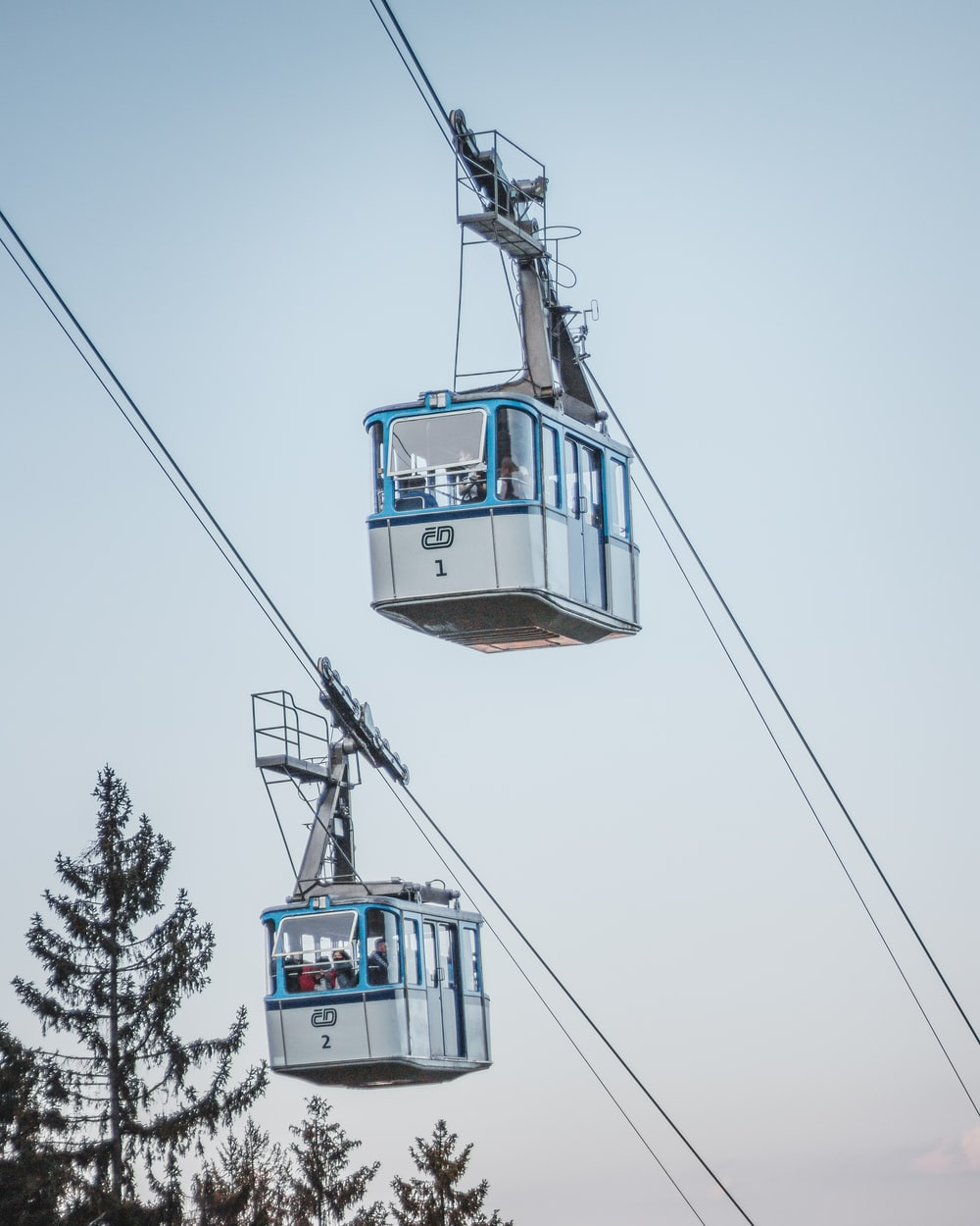 white and blue cable car under white sky