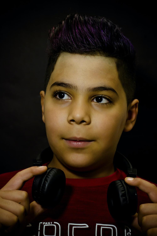 boy in red crew neck shirt holding black wireless headphones