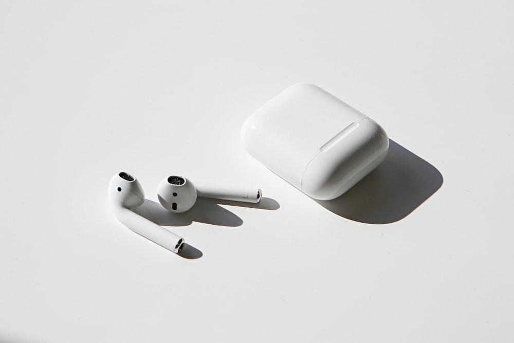 apple earpods beside apple airpods