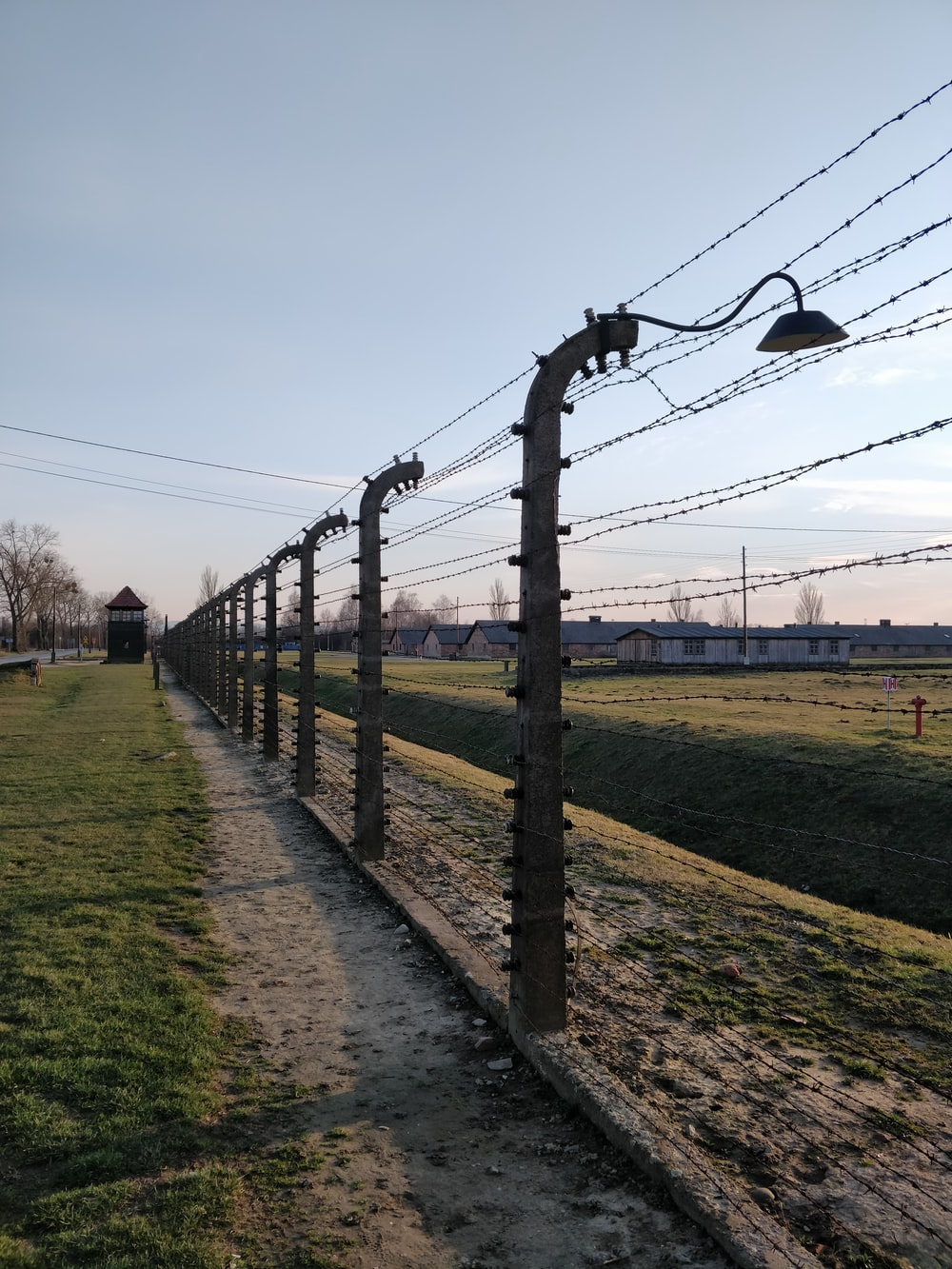 black metal fence on green grass field during daytime