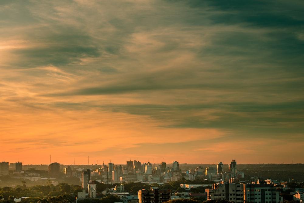 city skyline under cloudy sky during sunset