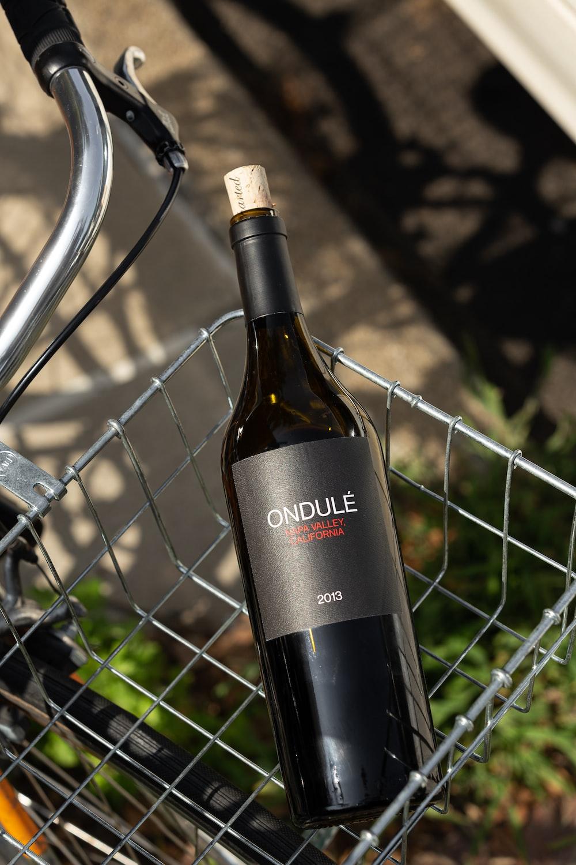 black glass bottle on gray metal fence