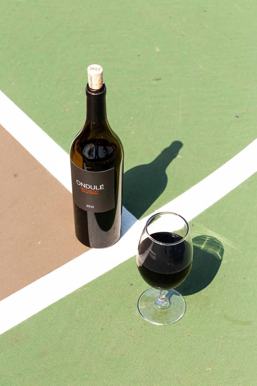 black glass bottle beside clear wine glass