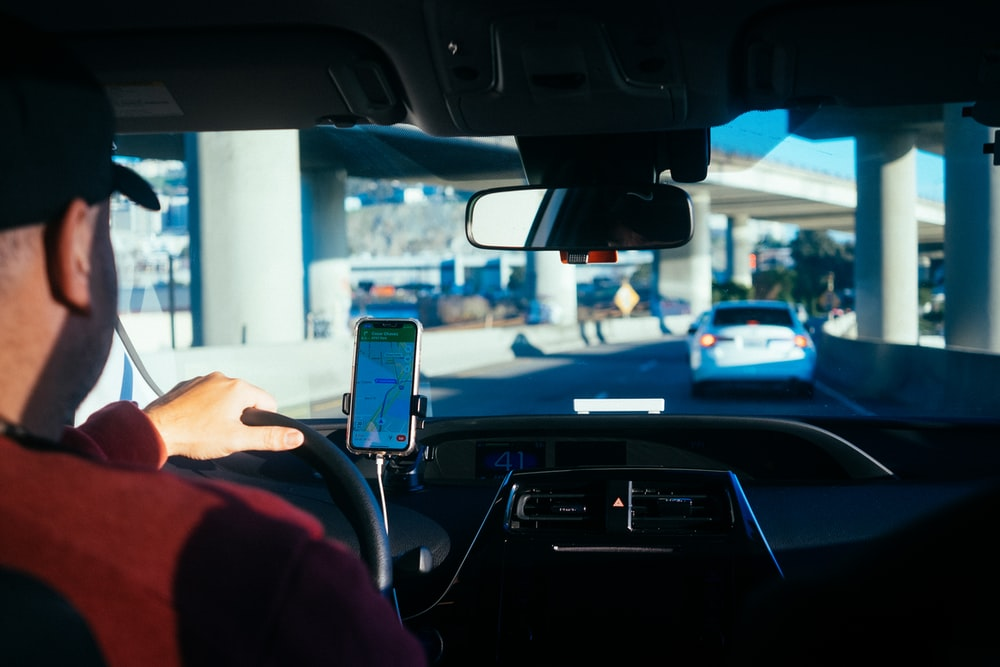 person holding iphone 6 inside car