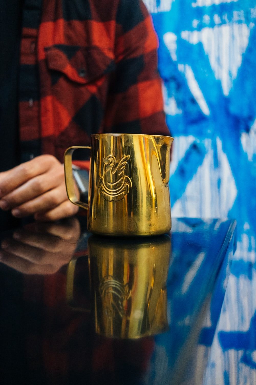 person holding gold and black ceramic mug