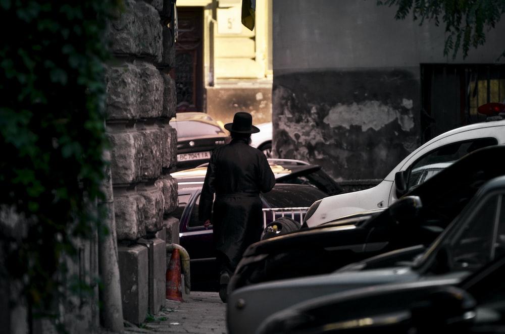 man in black jacket and brown hat standing beside black car during daytime