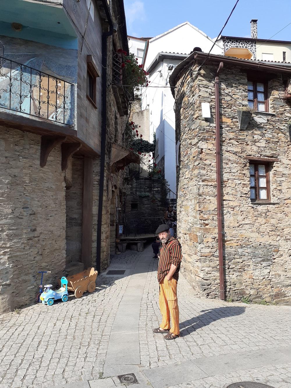 woman in brown dress walking on sidewalk during daytime