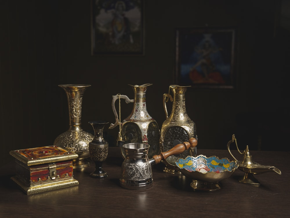 brass vase on brown wooden table