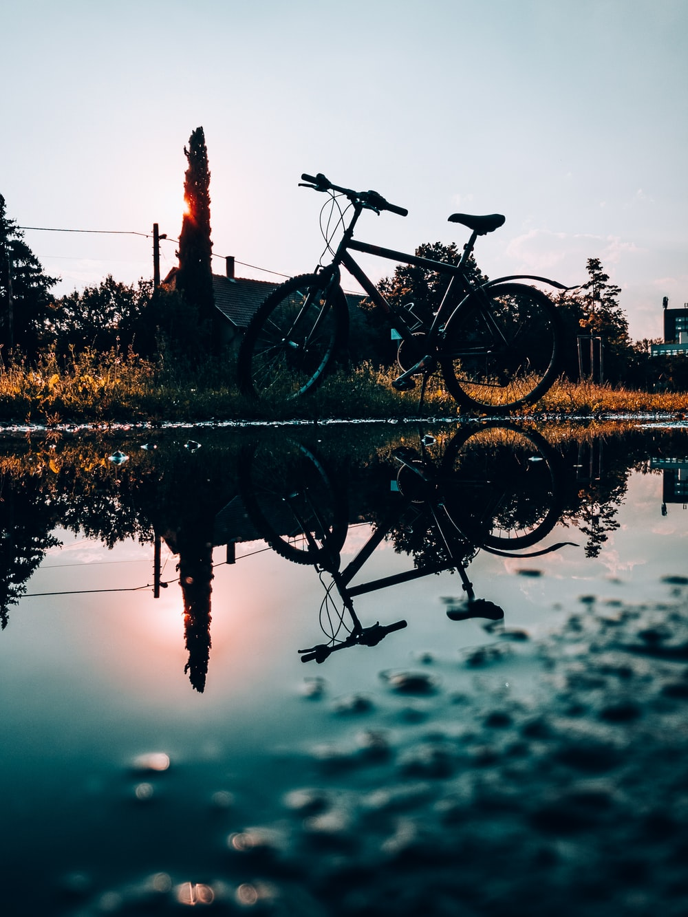 black bicycle on brown wooden fence near body of water during daytime