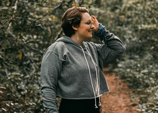 woman in gray hoodie standing on brown dried leaves during daytime