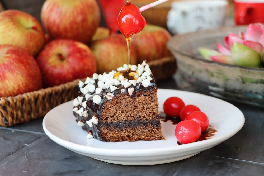 chocolate cake with cherry on white ceramic plate