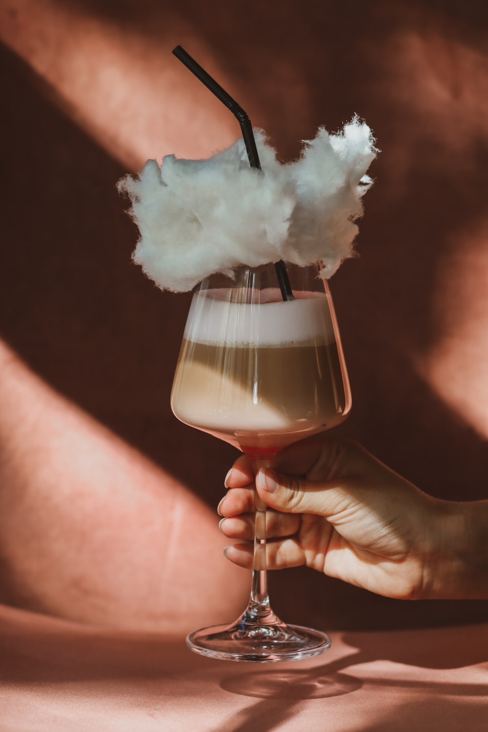 person holding clear wine glass with white smoke