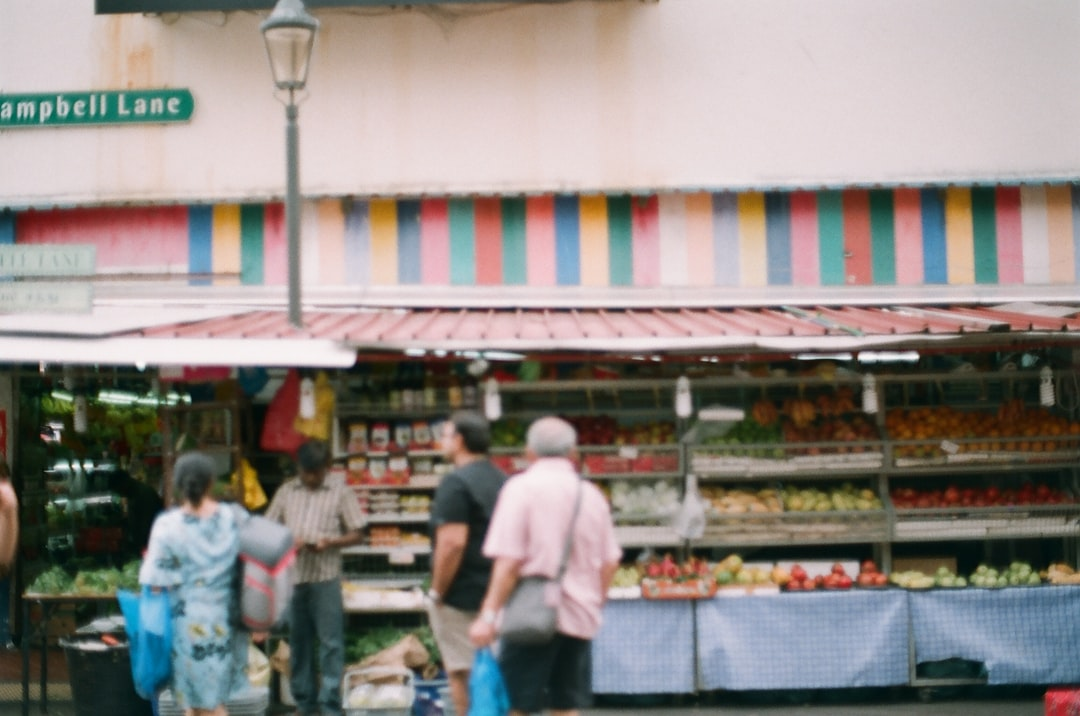 Man In White T-Shirt Standing Near Food Stall - unsplash