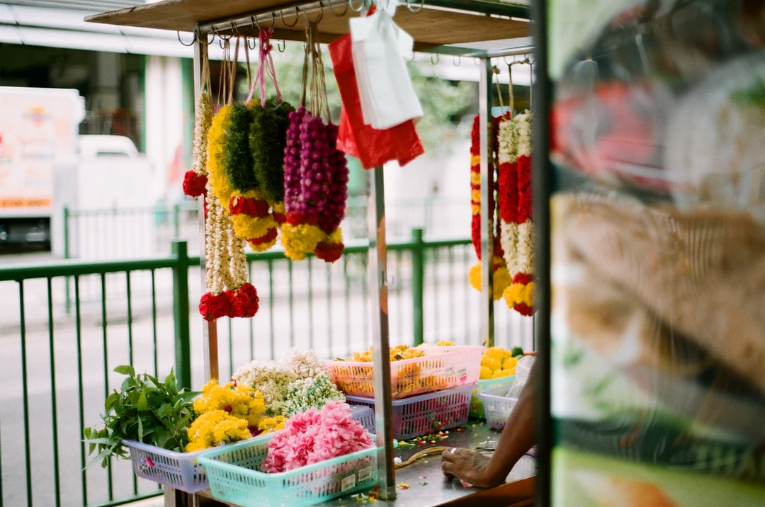 Woman In White and Green Floral Dress Standing Near Fruit Stand - unsplash