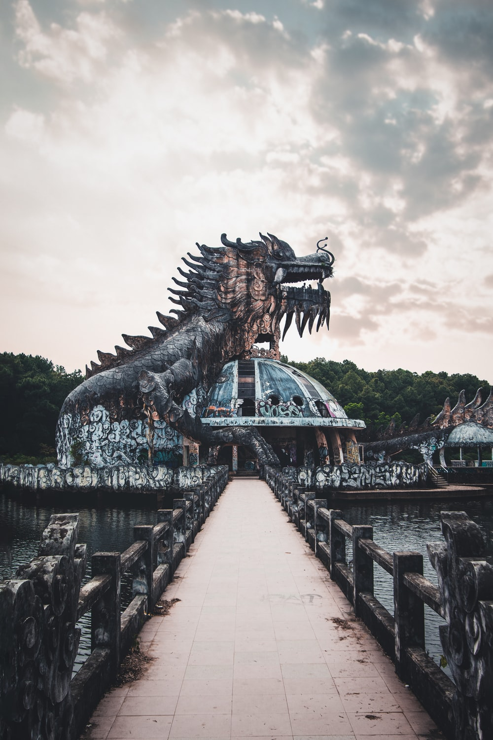 brown dragon statue near body of water during daytime