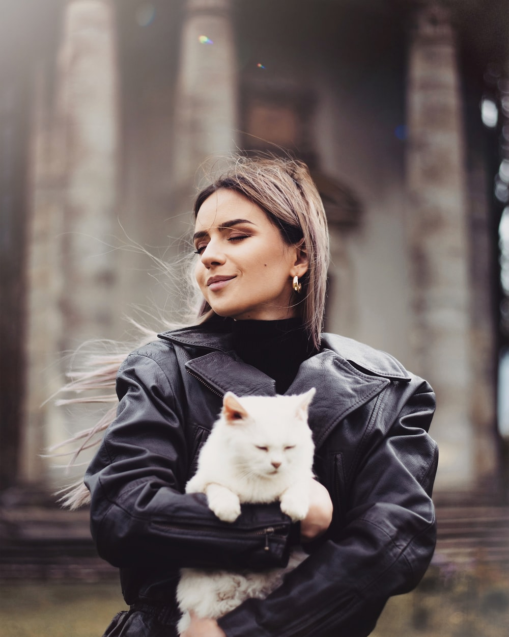 girl in black leather jacket holding white cat