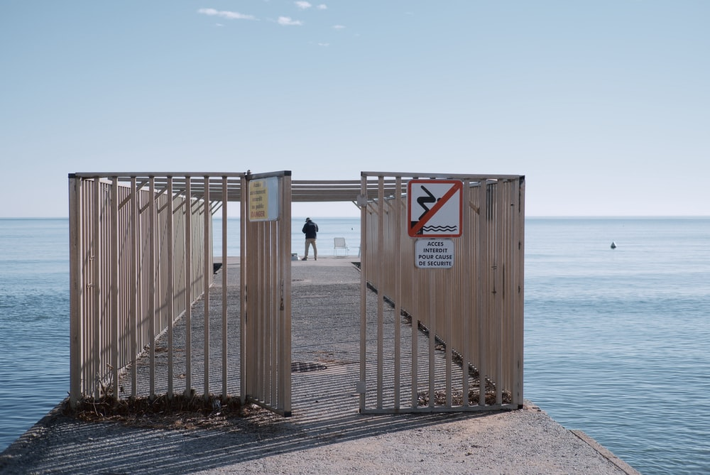 brown wooden fence near body of water during daytime