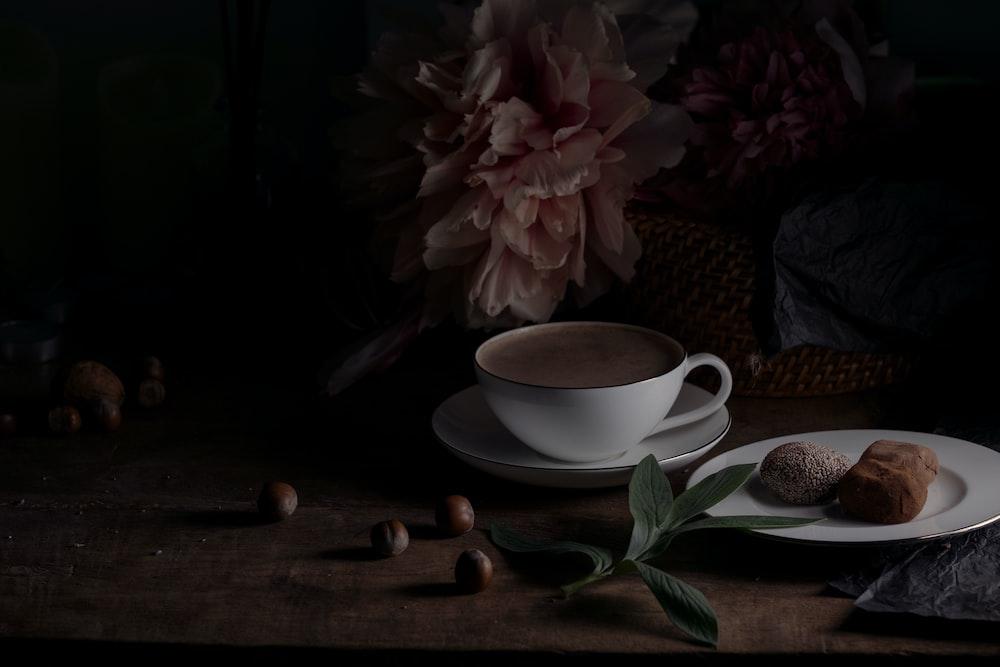 white ceramic teacup on saucer beside pink flower
