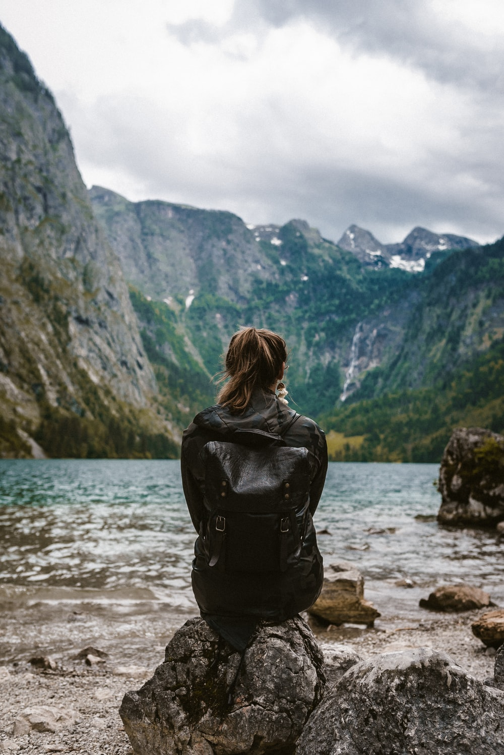 woman in black leather jacket standing on rock near body of water during daytime
