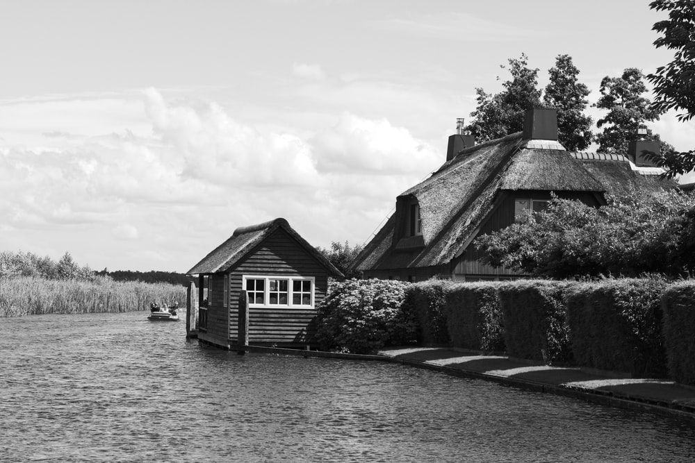 grayscale photo of house near body of water
