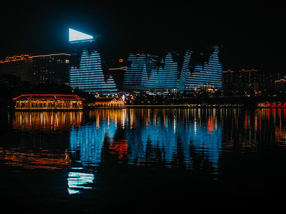 body of water near lighted building during night time