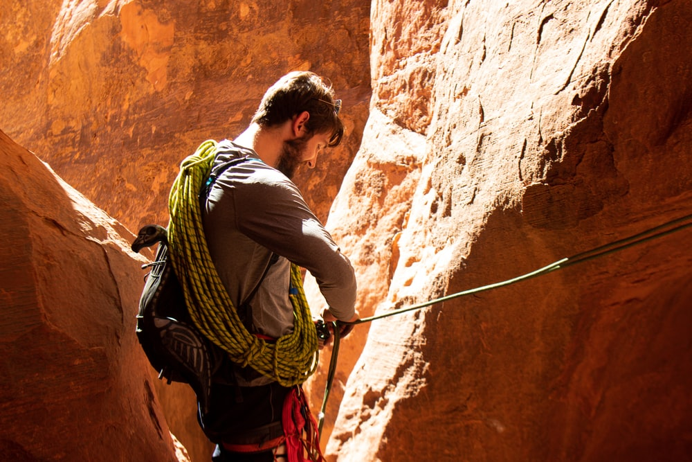 man in white t-shirt and green backpack climbing on brown rock